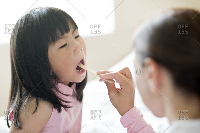 Young and nurse with tongue depressor