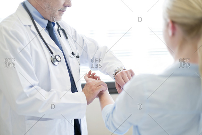 Male doctor taking patient's pulse