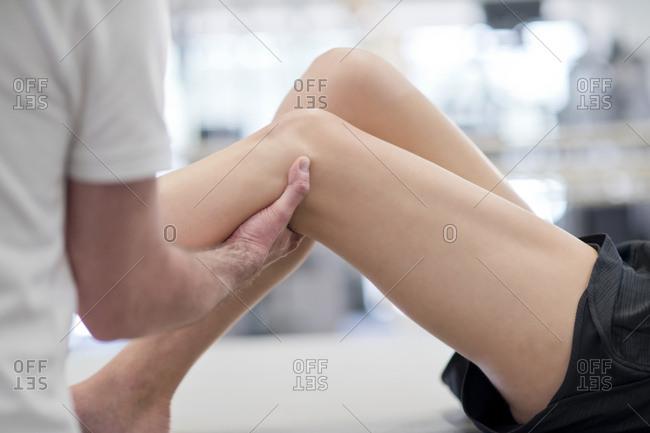 Physiotherapist massaging woman's leg