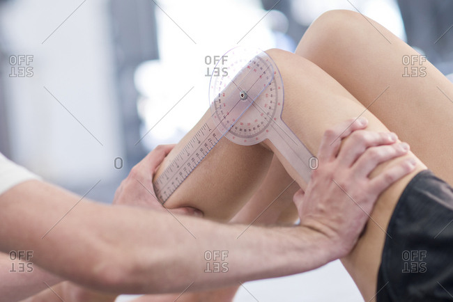 Physiotherapist measuring woman's leg