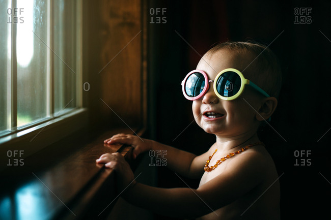 Baby girl at window in sunglasses