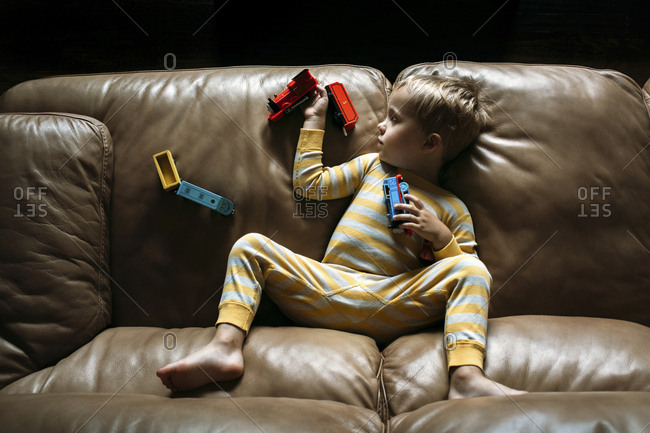 Boy sleeping on couch holding toy trains