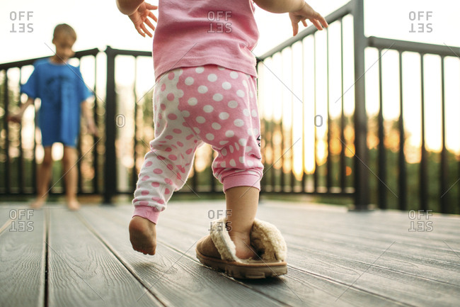 Little girl walking in one big slipper