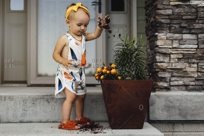Little girl digging in flower pot