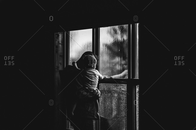 Dad holding girl by window on a rainy day