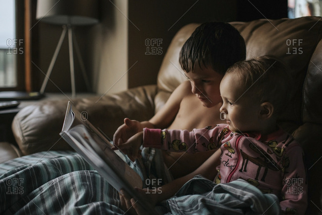 Siblings reading book together