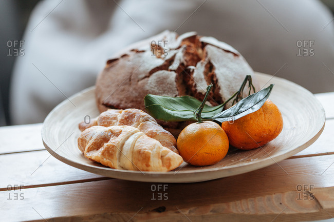 Fresh loaf of bread and croissants with oranges