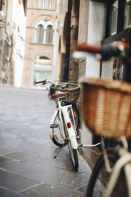 Bicycles parked at alley amidst buildings