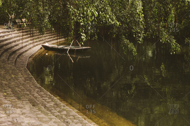 Boat moored by steps in lake