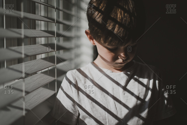 Boy standing by window at home