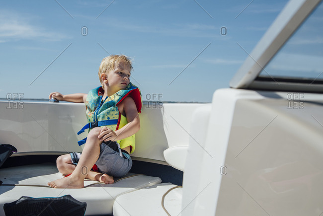 Boy wearing life jacket sitting in boat against blue sky
