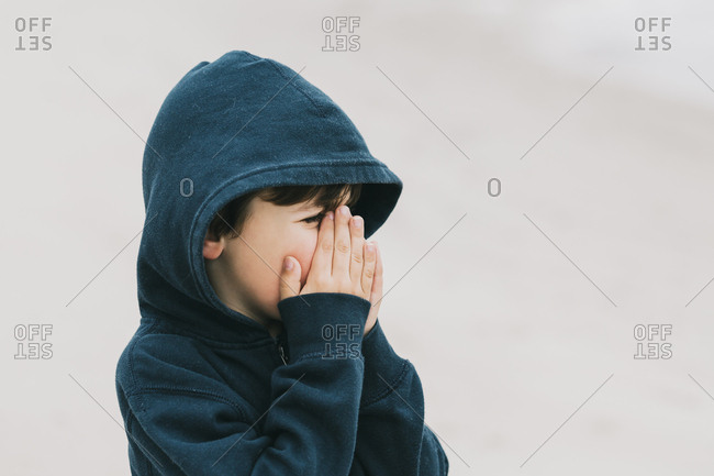 Boy with hands covering mouth standing at beach
