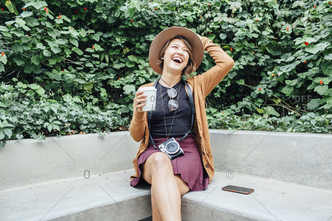 Cheerful woman holding disposable cup while sitting on bench at park