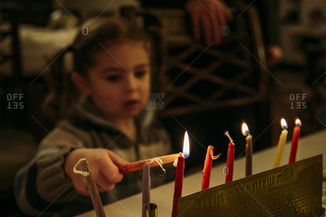 Close-up of girl igniting candles during Chanukah
