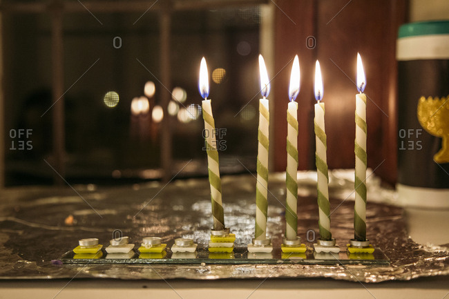 Close-up of illuminated candles on glass at table during Chanukah