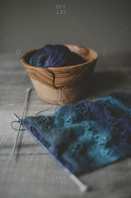 Close-up of knitted wool with needles on table