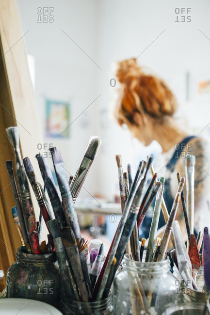 Close-up of paintbrushes with artist in background at studio