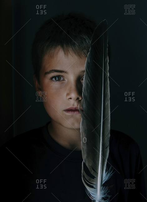 Close-up portrait of boy with feather in darkroom