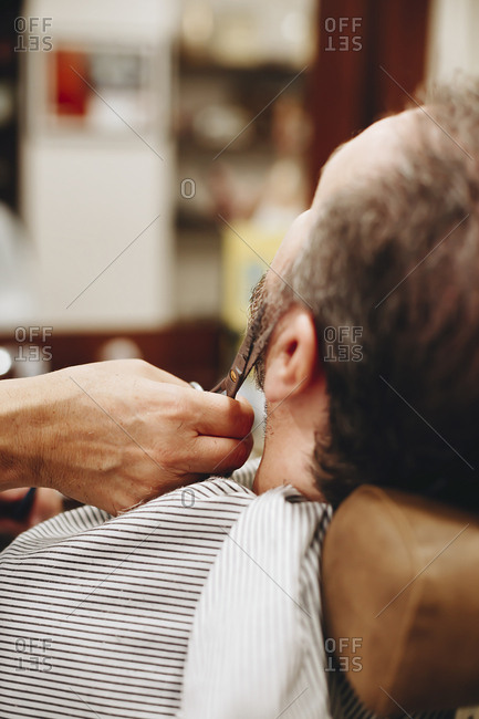 cropped hand of barber cutting man beard at salon