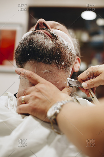 Cropped hands of barber shaving male customer at salon