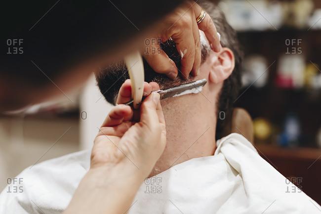 Cropped hands of barber shaving man at salon