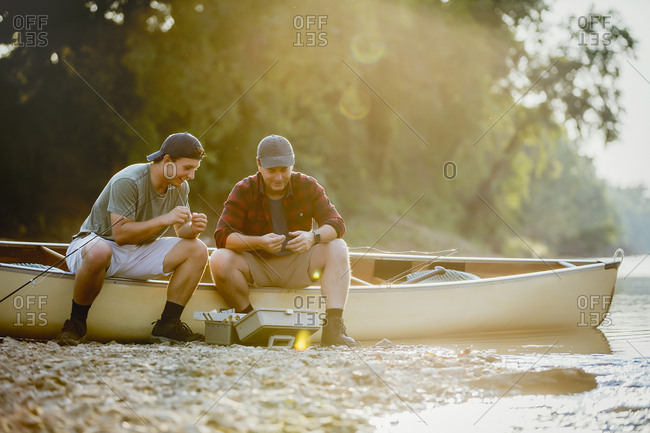 Friends adjusting fishing tackles while sitting on boat by lake