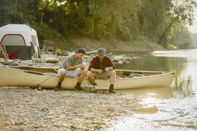 Friends adjusting fishing tackles while sitting on boat at campsite