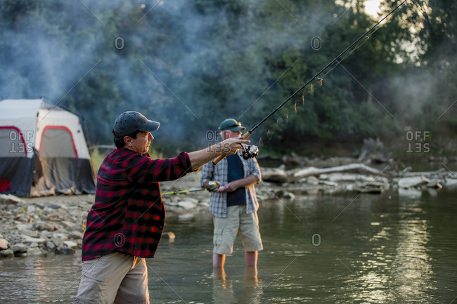 Friends fishing while standing in lake during sunset