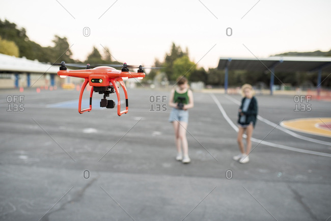 Friends flying quadcopter at park