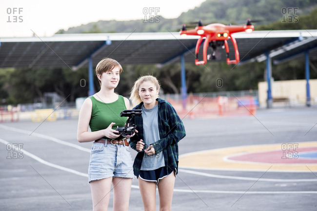 Friends operating quadcopter while standing at park