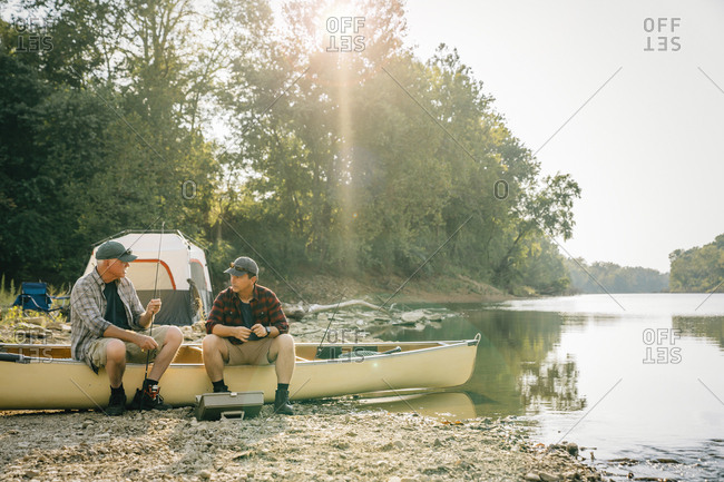 Friends with fishing rods talking while sitting on boat at campsite