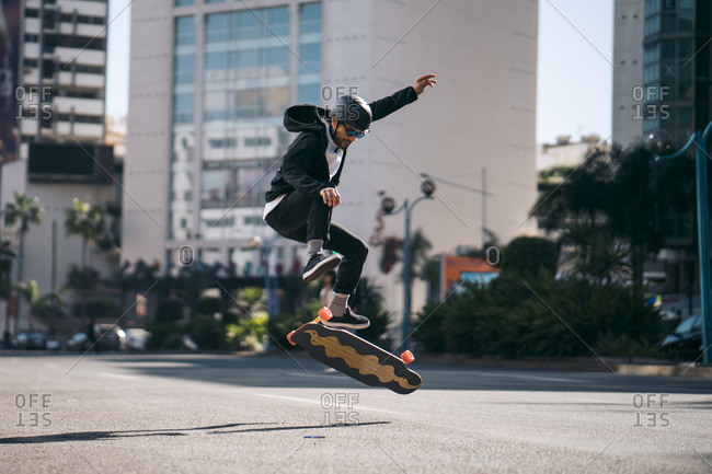 Full length of man performing stunt while skateboarding on road in city