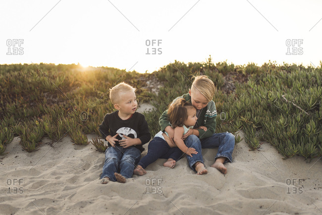 Full length of siblings sitting on sand at beach against clear sky during sunset