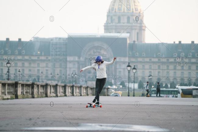 Full length of woman skateboarding against Musee de larmee