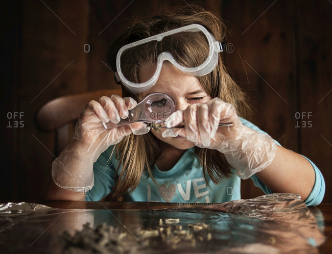 Girl looking at object through magnifying glass while sitting at table