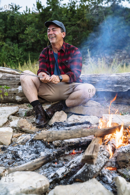 Happy mid adult man cooking fish on campfire