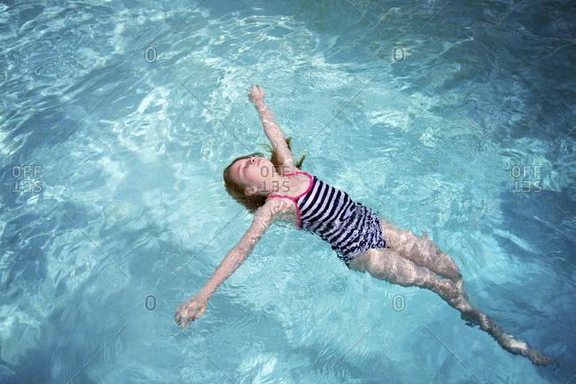 High angle view of girl in swimwear swimming in pool