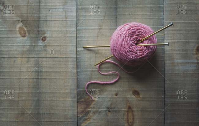 High angle view of woolen ball with knitting needles on table