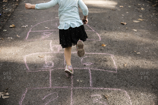 Low section of girl playing on hopscotch