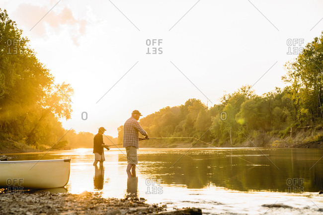 Make friends fishing while standing in lake against sky during sunset