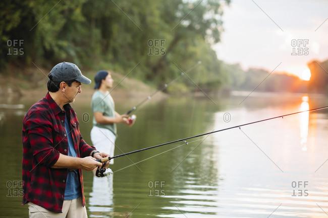 Male friends fishing in lake
