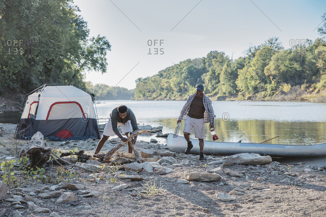 Male friends enjoying at campsite by lake