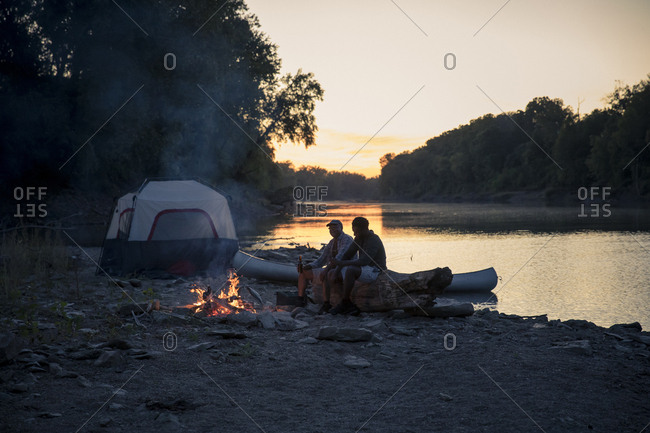 Male friends relaxing at campsite by lake against sky during sunset
