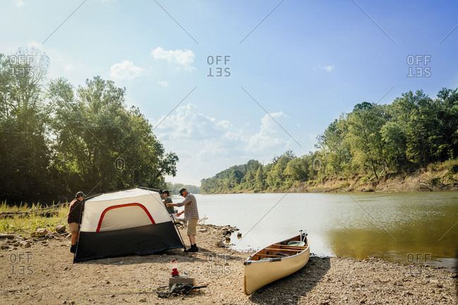 Male friends standing by tent at lakeshore against sky
