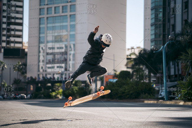 Man performing stunt while skateboarding on road in city