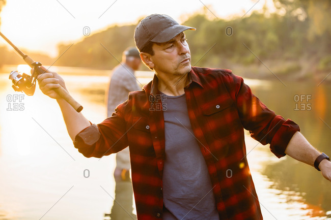 Mid adult man fishing while friend standing in background during sunset