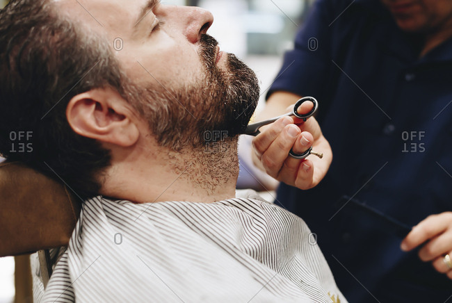 Midsection of barber cutting man beard at salon