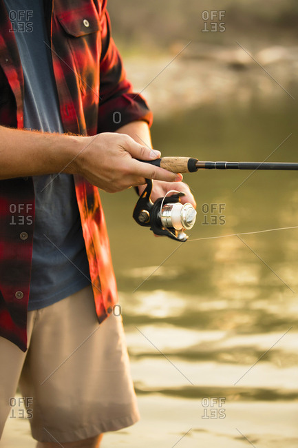 Midsection of mid adult man fishing while standing in lake