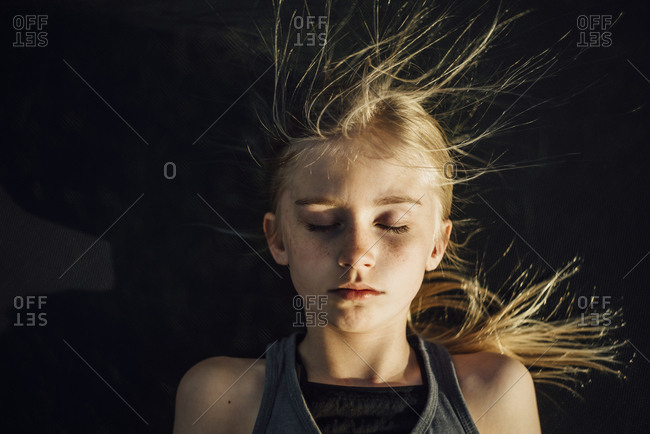 Overhead view of girl with eyes closed and tousled hair during sunny day