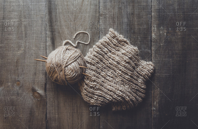 Overhead view of woolen ball by knit hat on table